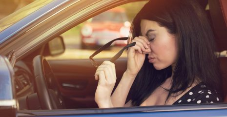 Woman having headache taking off glasses after driving car in traffic jam