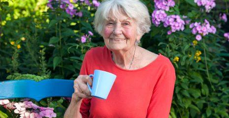 Elderly lady having a coffee in the garden