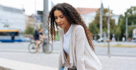 Trendy young woman sitting on an urban bridge