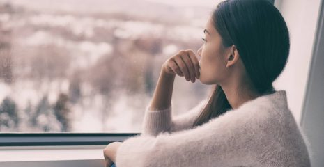 woman sad comtemplative looking out the window alone